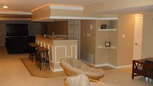 Modern basement after remodel design with low ceiling and light brown interior color plus mini bar with marble countertop table and wood bar stools plus rattan egg lounge