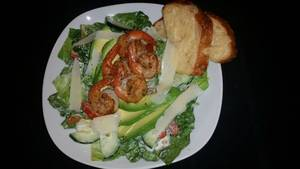 Caesar salad with grilled prawns   avocado served with  garlic parmesan bread