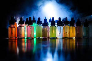 82740171 vape concept smoke clouds and vape liquid bottles on dark background light effects useful as backgro