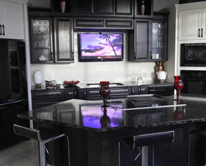 Modern dark wood kitchen with television